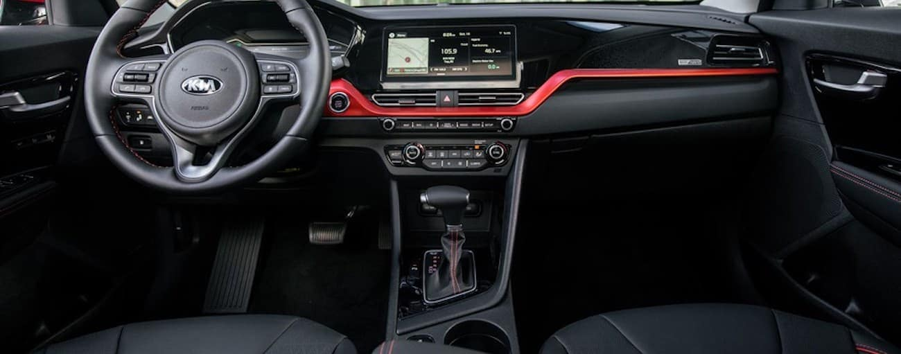 The black and red dashboard in the interior of a 2020 Kia Niro is shown.