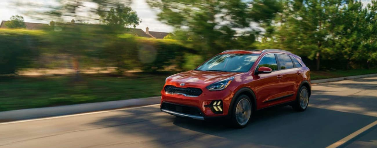 A red 2020 Kia Niro is driving on a tree-lined street near Freehold, NJ.