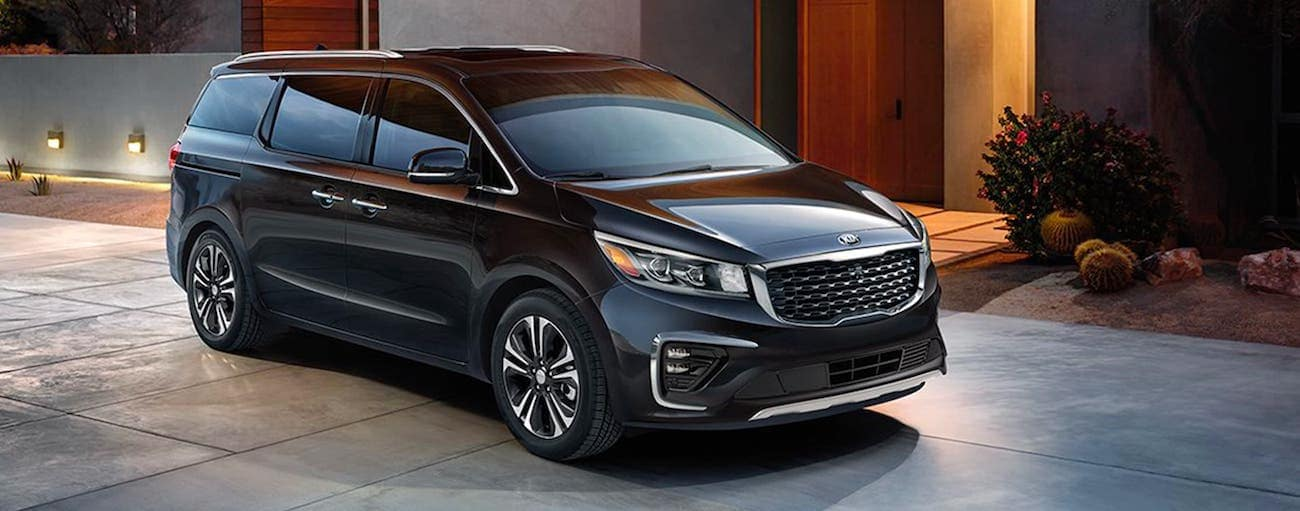 A black 2020 Kia Sedona is parked in a modern driveway outside Freehold, NJ.