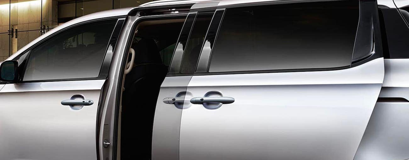A silver 2020 Kia Sedona is simulating the automatic doors.