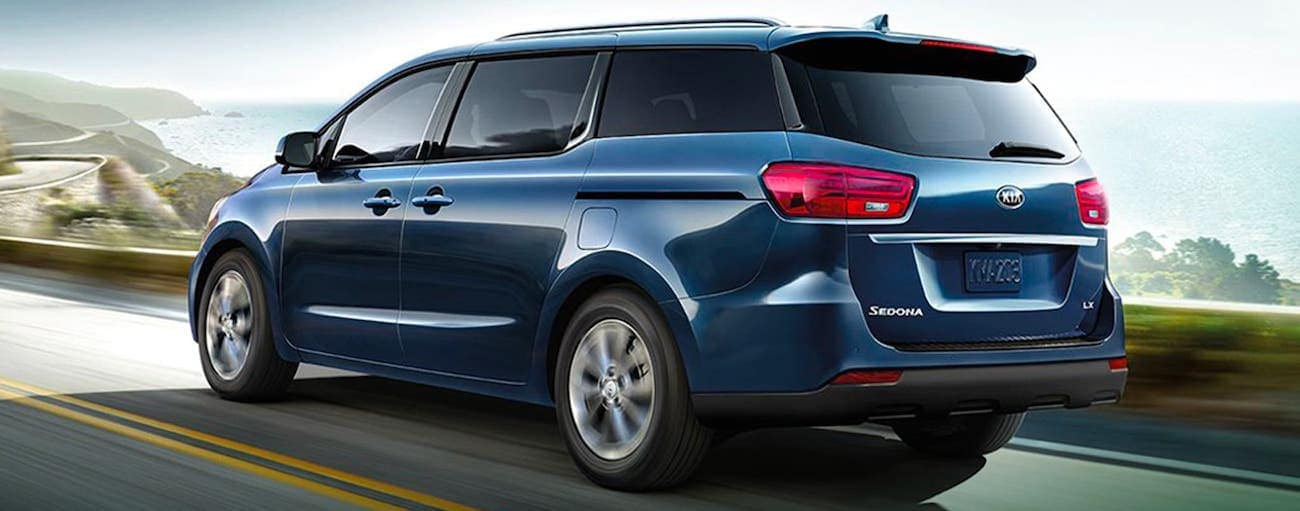 A blue 2020 Kia Sedona is driving on a highway next to an ocean outside Freehold, NJ.
