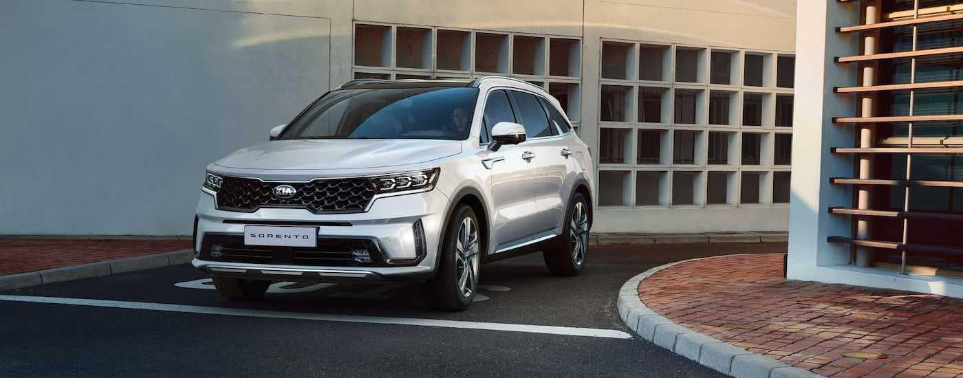 A white 2021 Kia Sorento is driving out of a parking garage after leaving a Kia dealership near me.