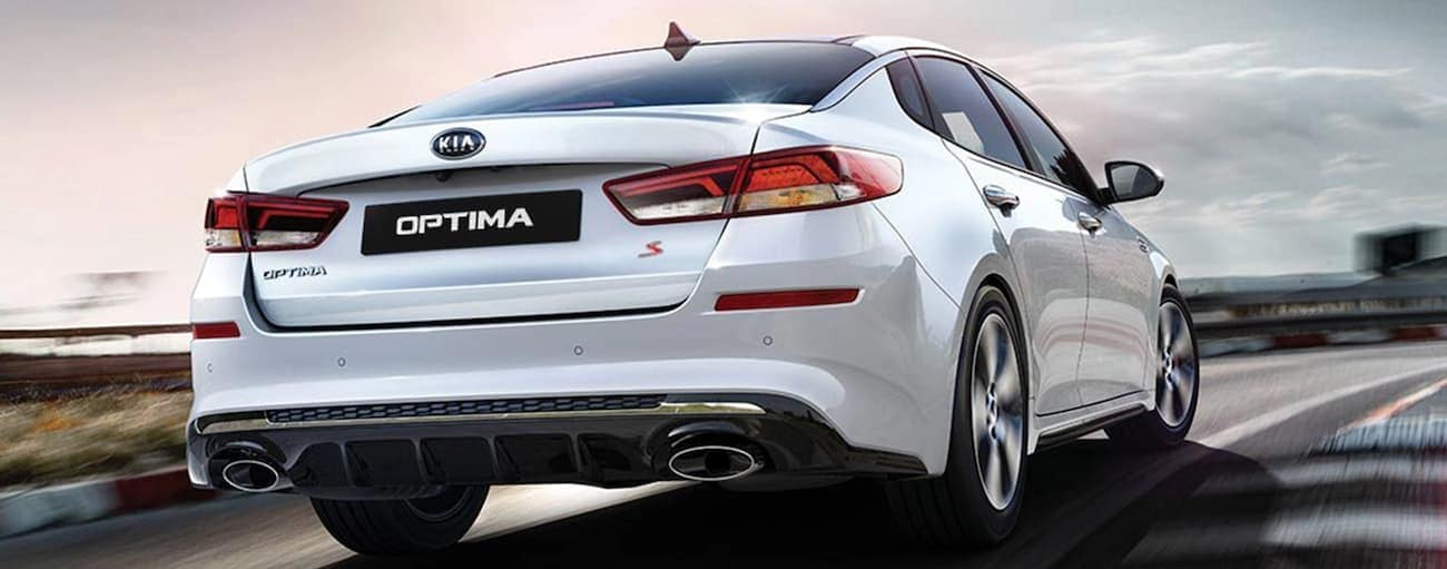 A white 2020 Kia Optima is driving on a highway near Freehold, NJ.