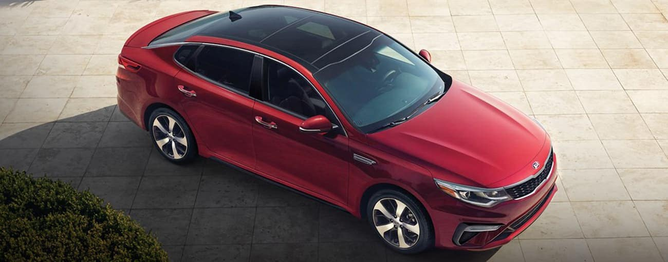A red 2020 Kia Optima is parked on tan pavers after winning the 2020 Kia Optima vs 2020 Ford Fusion comparison.