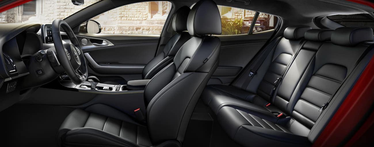 The black interior of a 2020 Kia Stinger is shown from the side.