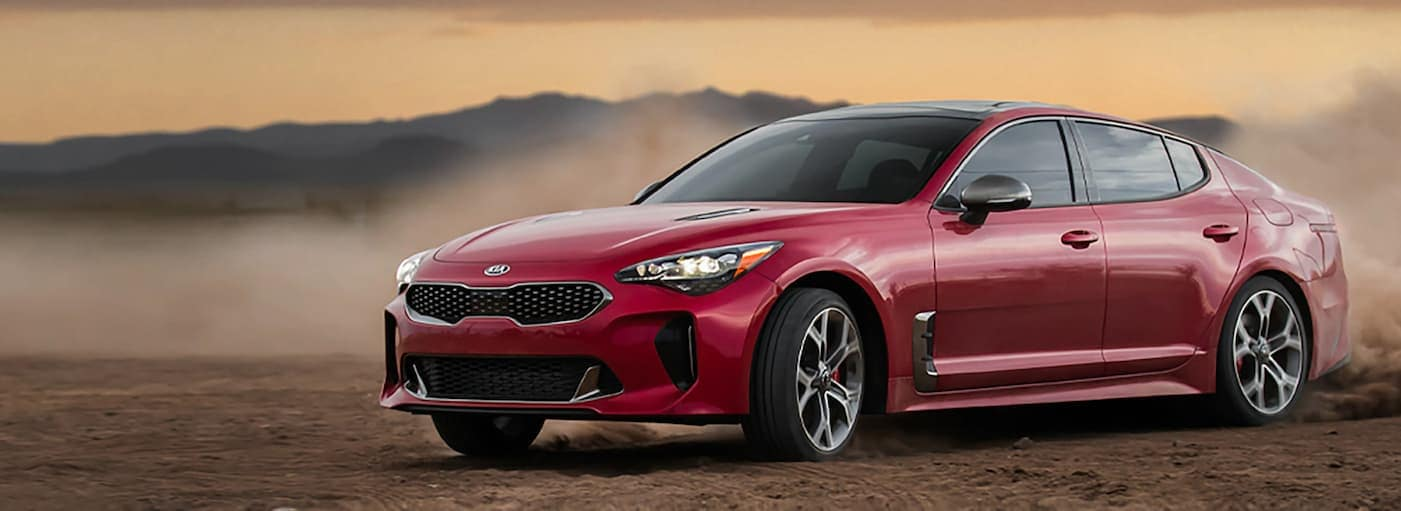 A red 2020 Kia Stinger is driving off-road in the dirt.