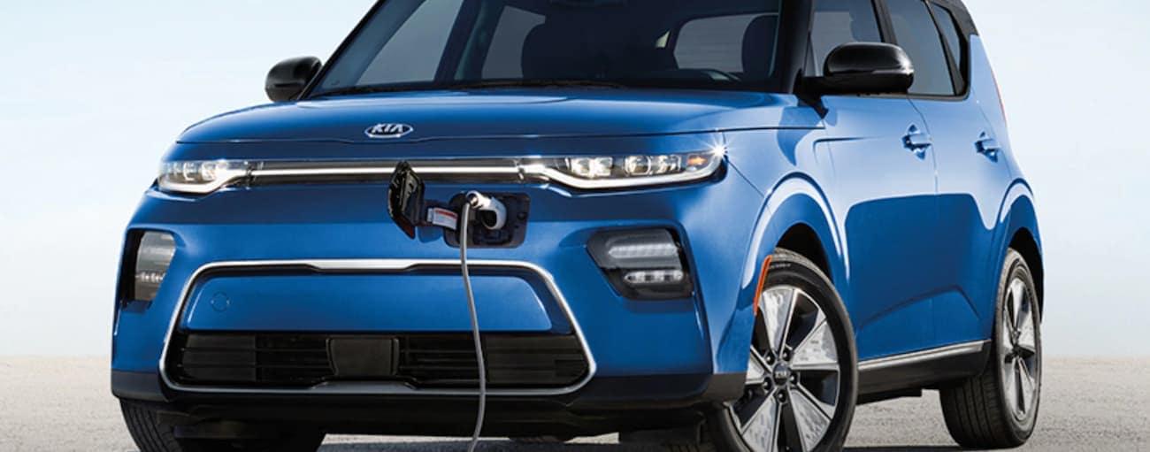 A blue 2021 Kia Soul EV is charging in Freehold, NJ.