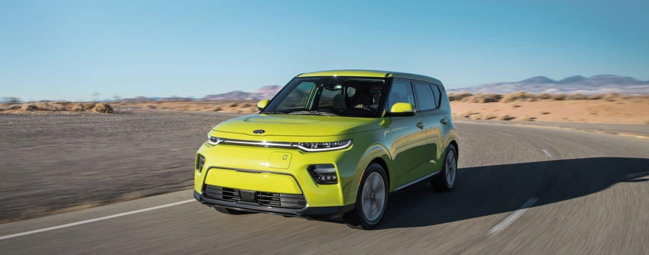 A bright green 2021 Kia Soul EV is driving on a desert road.