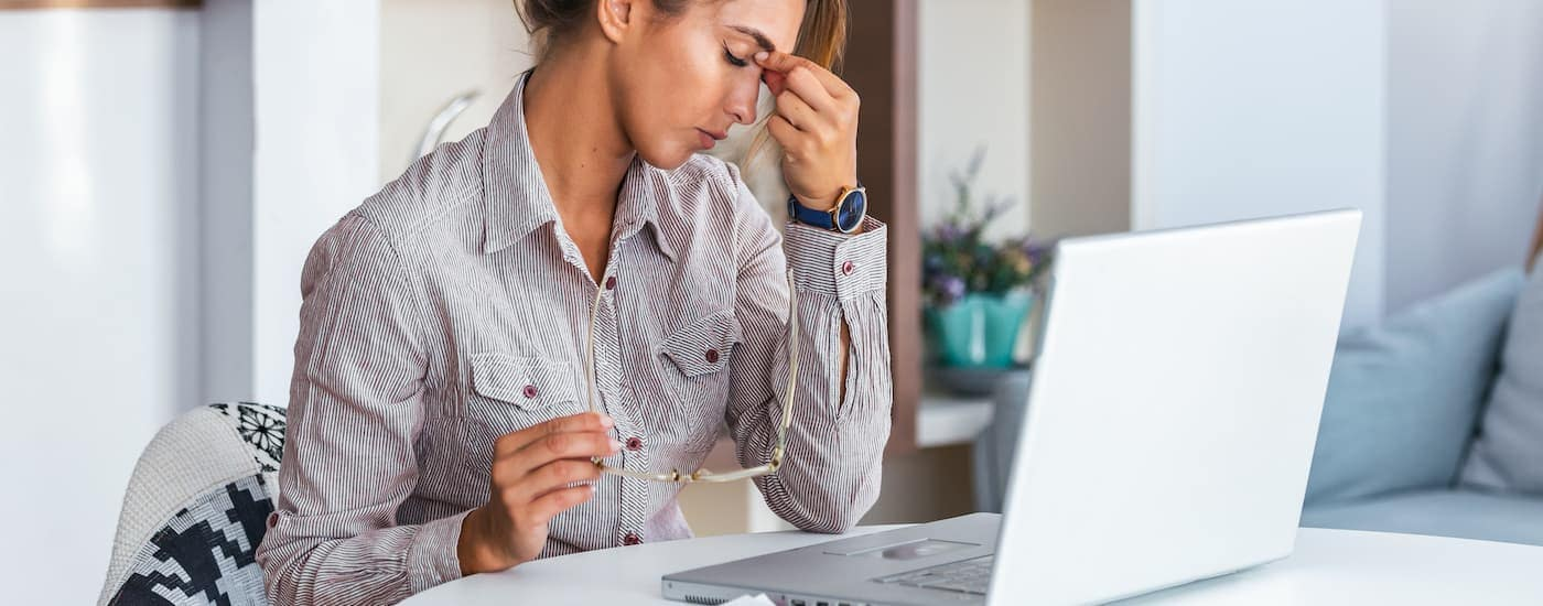 A woman is frustrated on a laptop.