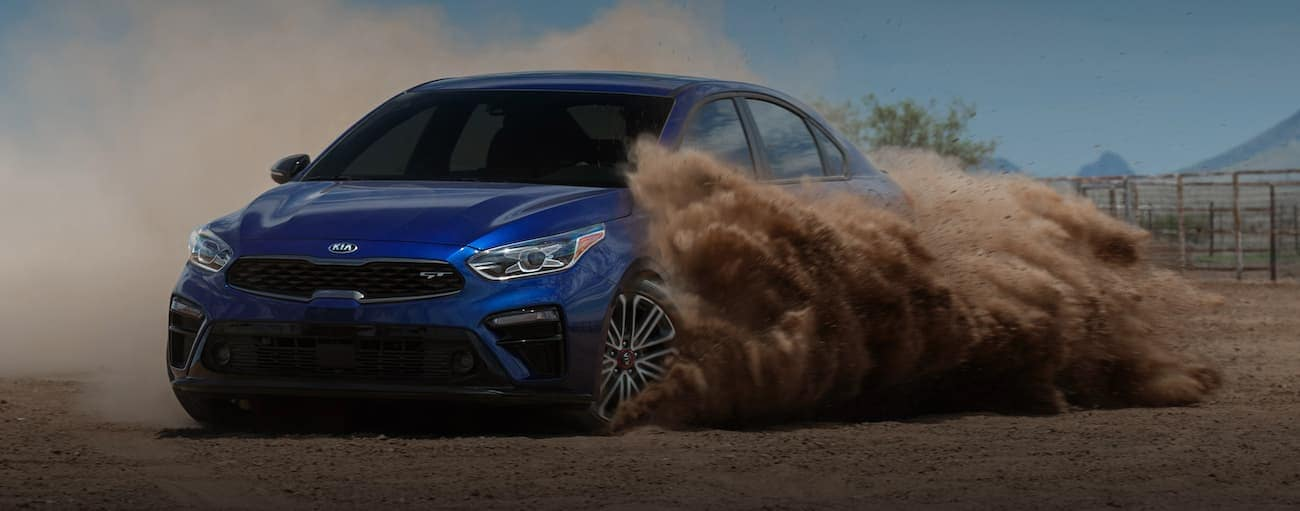 A blue 2020 Kia Forte is drifting in the dirt outside Freehold, NJ.