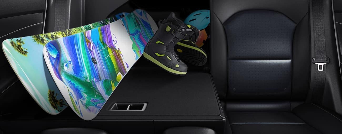 Snowboard gear is shown coming through the folded down back seat of a 2020 Kia Forte.