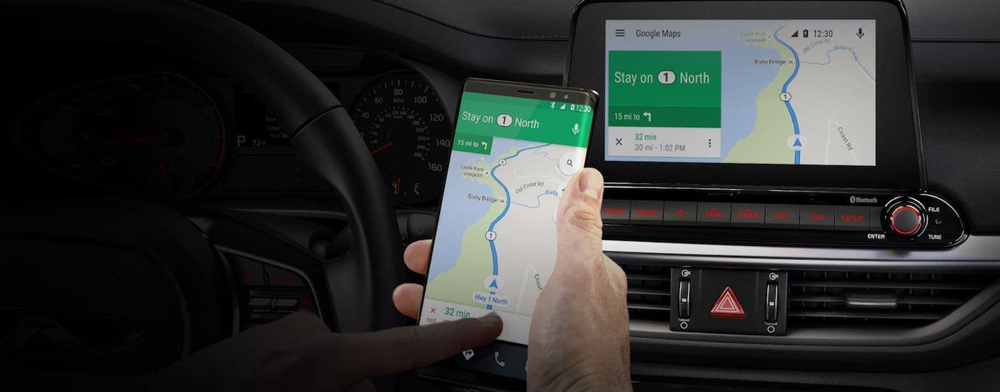 A driver is using his phone to get directions that appear on the touchscreen inside a 2020 Kia Forte.