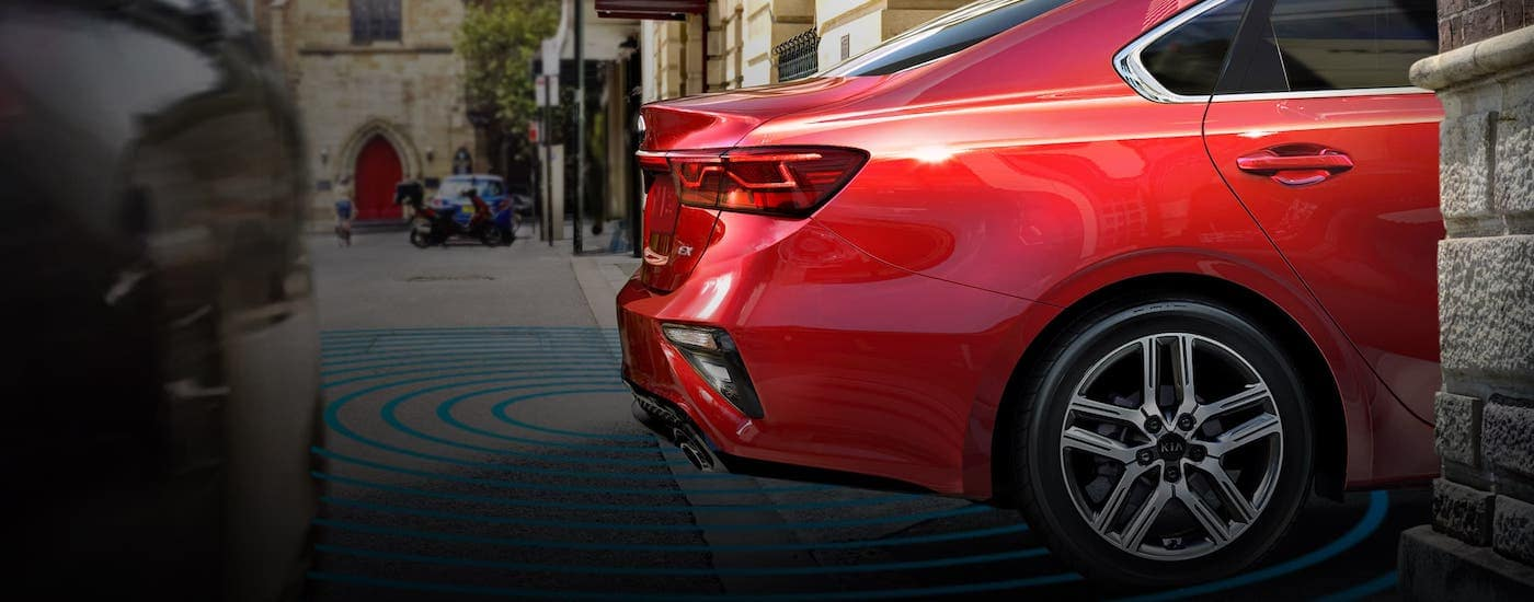 A red 202 Kia Forte is backing onto a Freehold, NJ, road with simulated safety lines around the rear end.