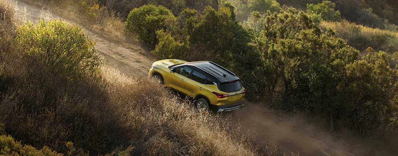 A yellow 2021 Kia Seltos is driving fast up a dirt road after winning the 2021 Kia Seltos vs 2020 Kia Sportage comparison.