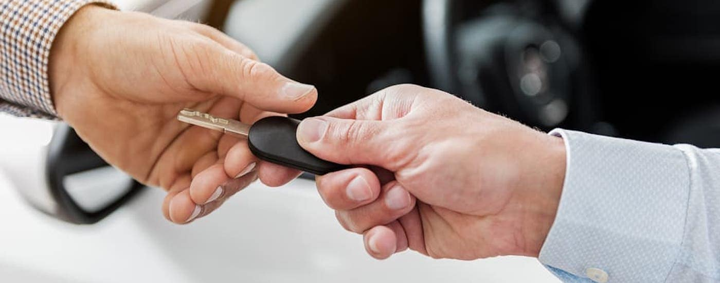 A close up is shown of a car key being handed over at an end of lease turn-in.