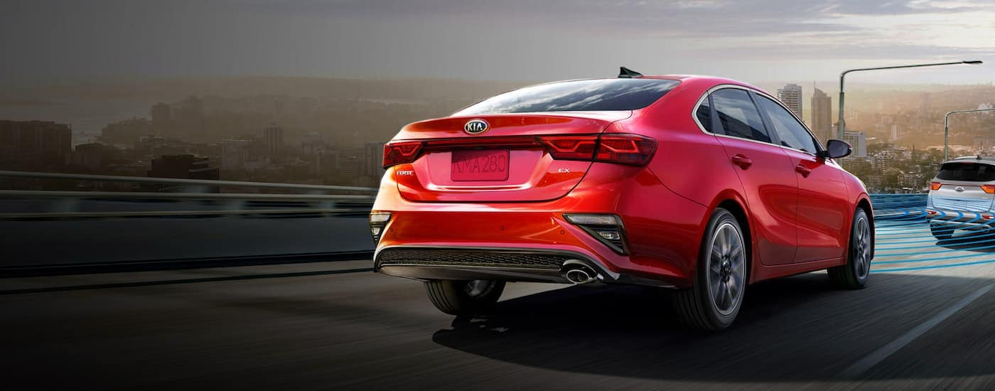 A red 2020 Kia Forte is driving on a highway into a city.