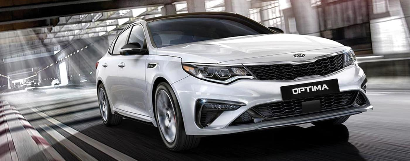 A white 2020 Kia Optima, which is popular among Kia car models, is driving on a covered highway near Freehold, NJ.