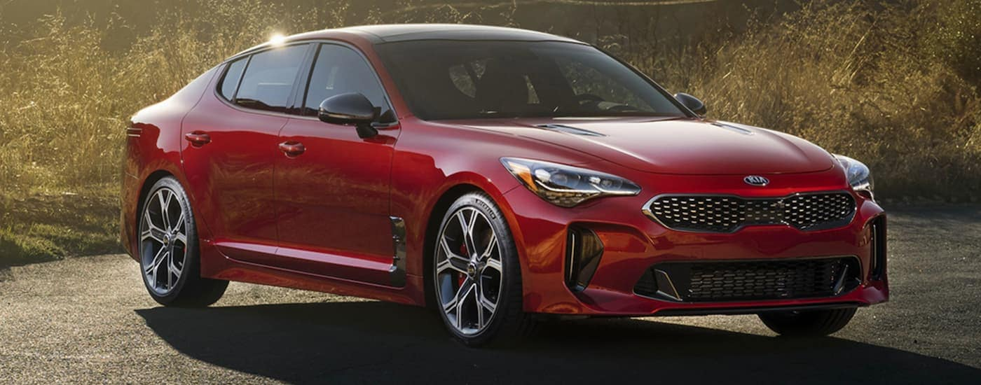 A red 2020 Kia Stinger is parked in front of tall grass with sun shining through.
