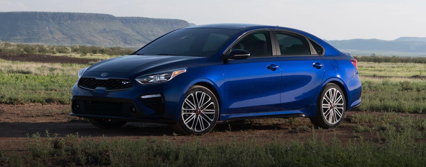 A blue 2020 Kia Forte is parked in a field.