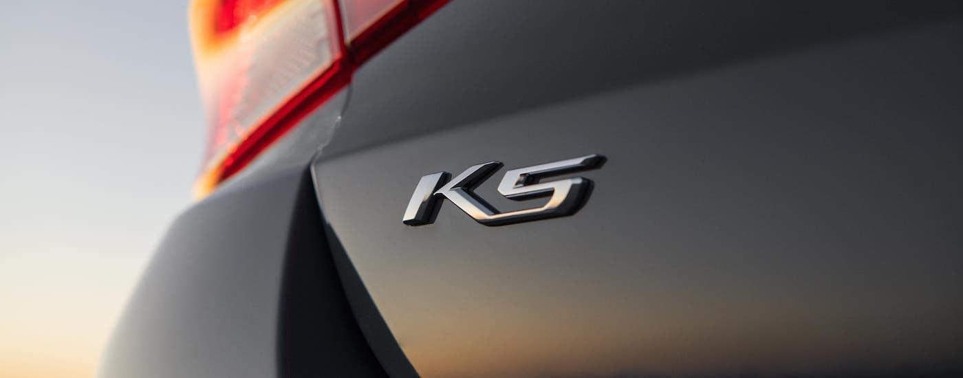 A closeup shows the rear badging on a dark gray 2021 Kia K5 at sunset.