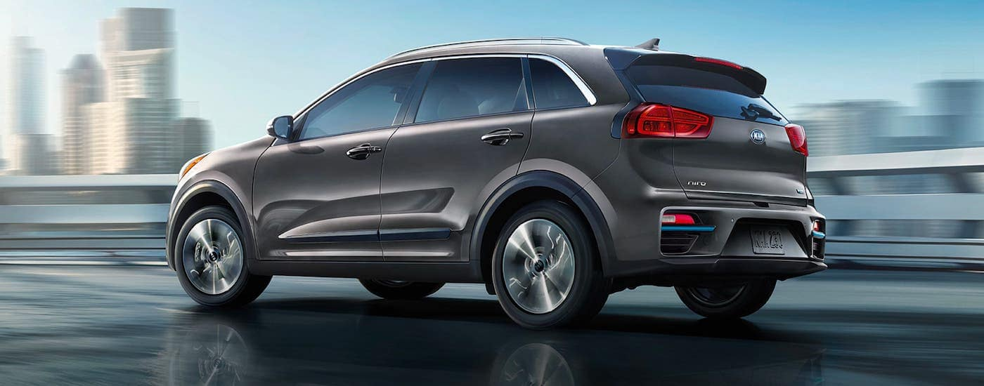 A gray 2020 Kia Niro EV is driving on a highway in front of a city.