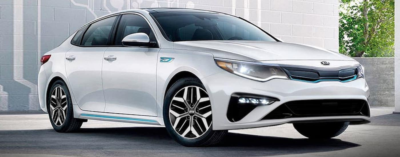 A white 2020 Kia Optima, one of the hybrid Kia car models, is parked in front a white wall with art on it.
