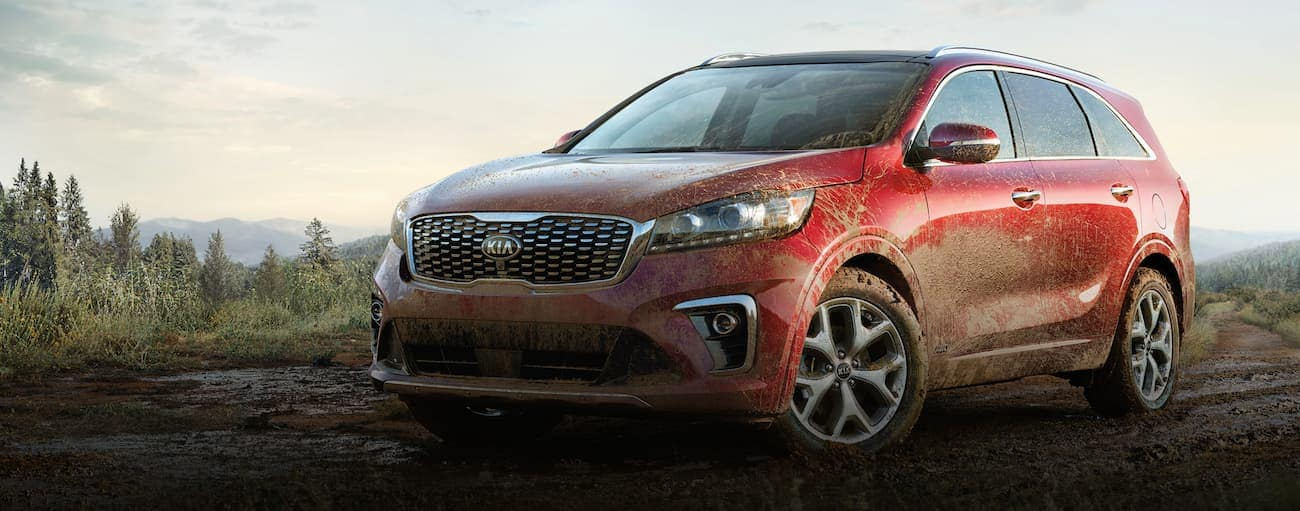 A red 2020 Kia Sorento is parked off-road in the mud after winning the 2020 Kia Sorento vs 2020 Mazda CX-9 comparison.