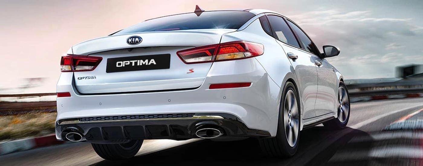 The rear of a white 2020 Kia Optima is shown driving on a highway.