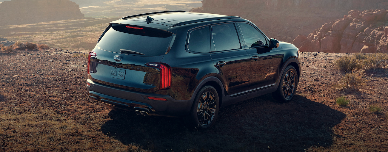 A black 2021 Kia Telluride is parked in a desert overlooking a cliff.