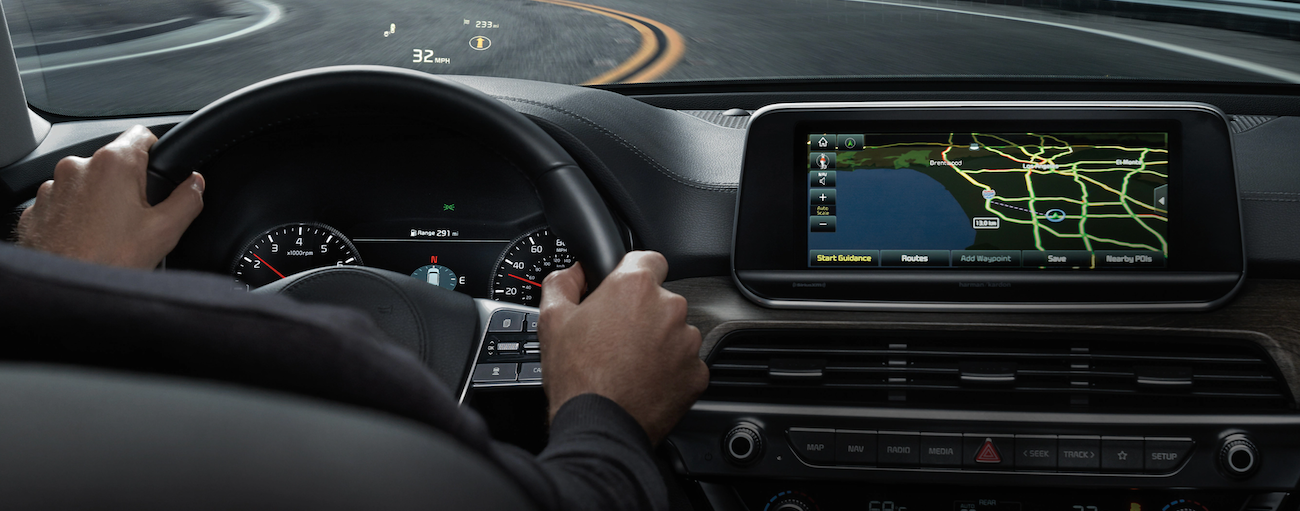 The head-up display and GPS are shown in a 2021 Kia Telluride while driving on a winding road in Freehold, NJ.