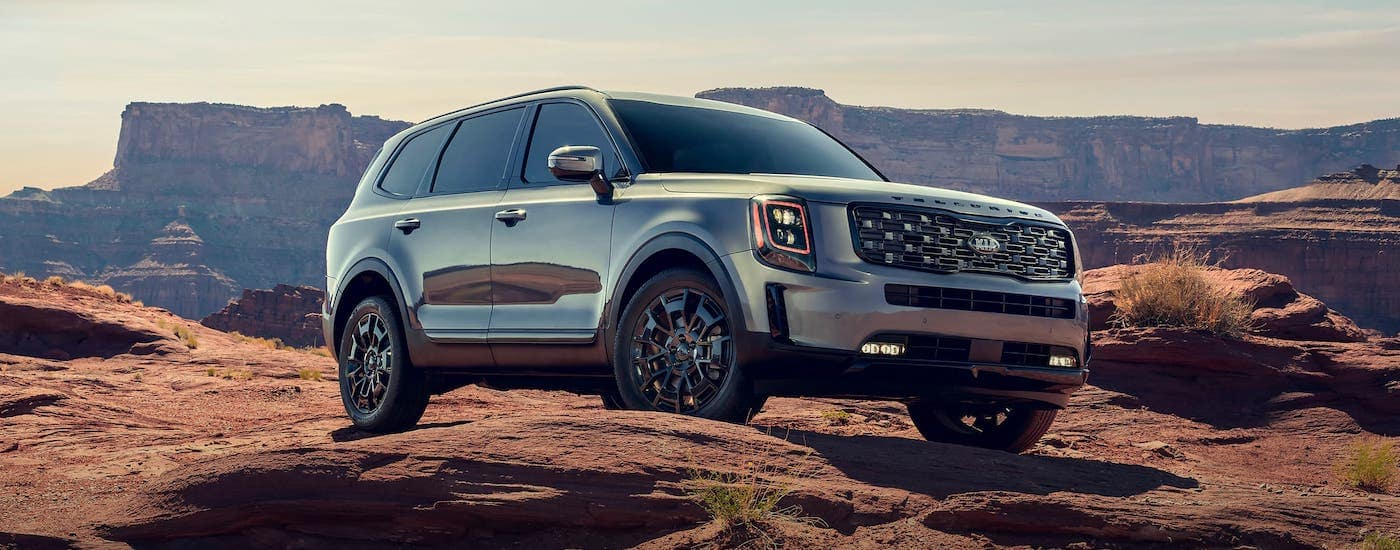 A silver 2021 Kia Telluride is climbing over rocks in front of a canyon.