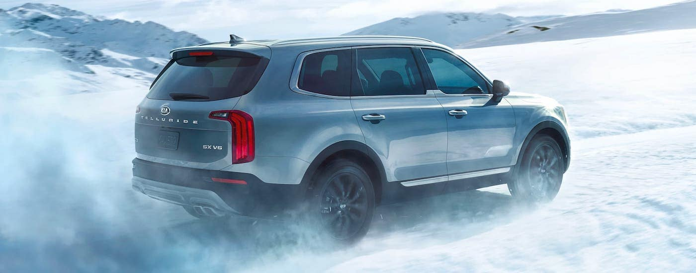 A silver 2021 Kia Telluride is driving in the snow after winning the 2021 Kia Telluride vs 2020 Ford Explorer comparison.