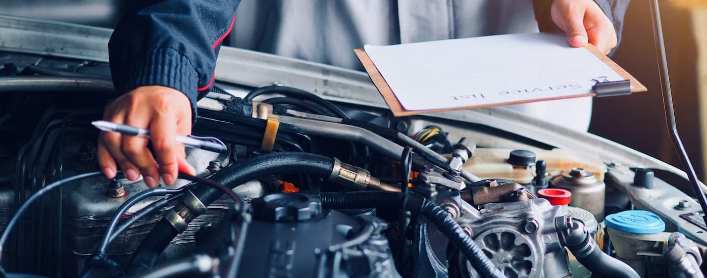 A mechanic with a clipboard is checking under the hood of a car.