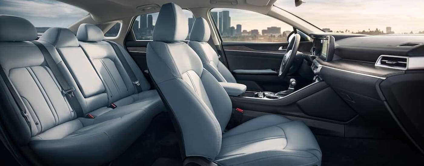The white and black interior of a 2021 Kia K5 is shown from the side.