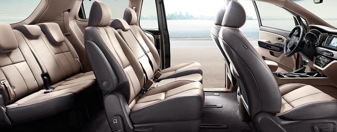 The three rows of tan seats in a 2021 Kia Sedona are shown from the side.