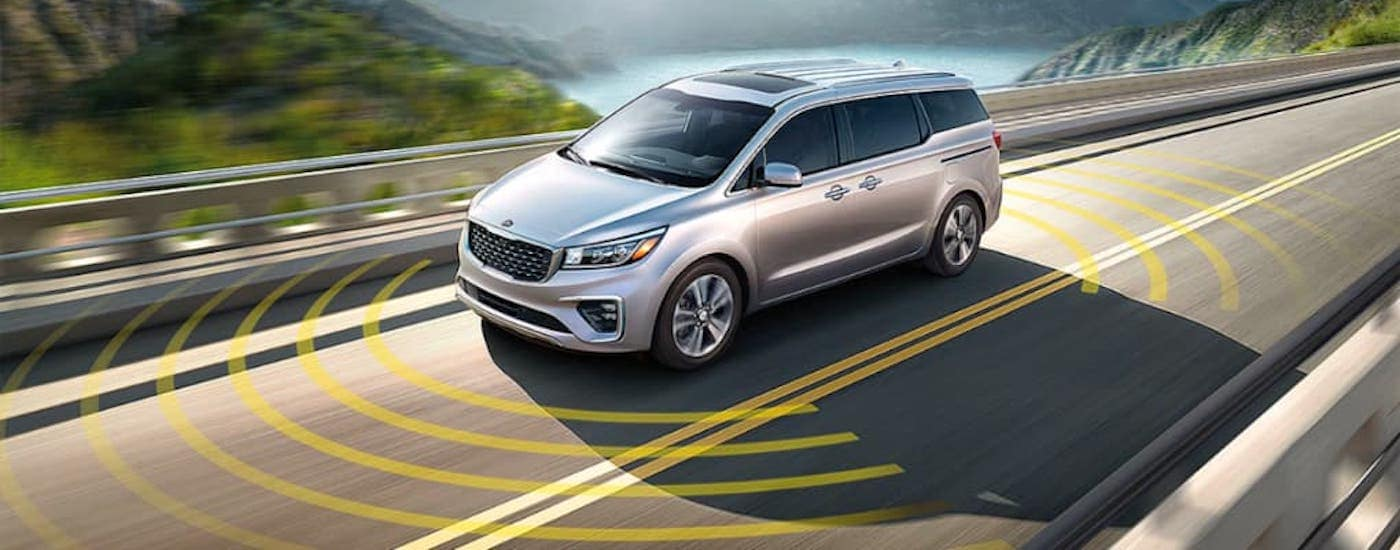 A silver 2021 Kia Sedona is shown driving on a highway with simulated safety sensor lines around it.