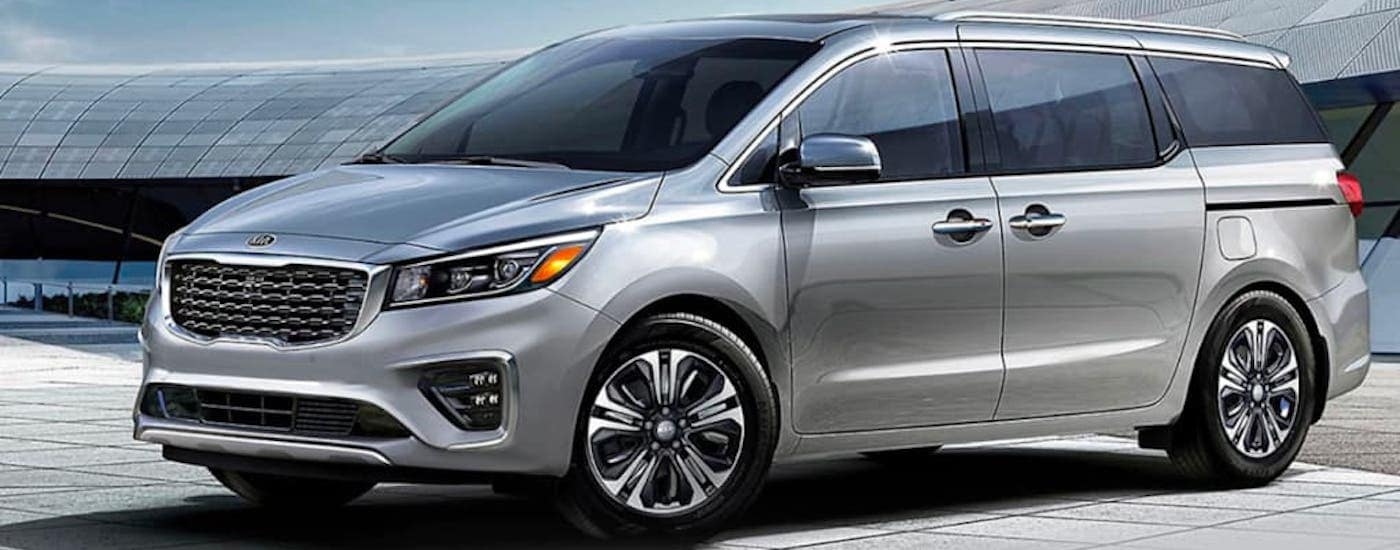 A silver 2021 Kia Sedona is parked in front of a hangar near Freehold, NJ.