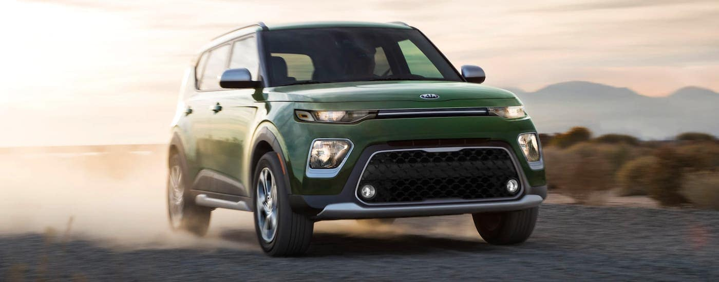 A green 2021 Kia Soul is driving on a desert road.