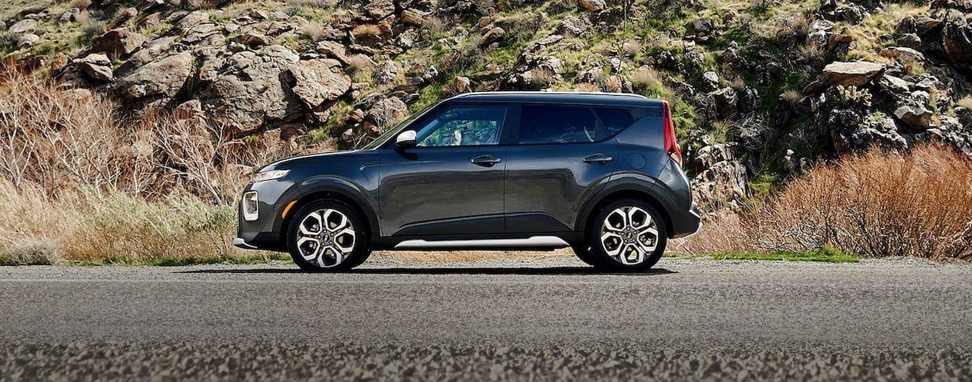 A black 2021 Kia Soul is shown from the side in front of a rock wall near Freehold, NJ.