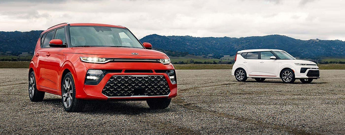 A red and a white 2021 Kia Soul are parked on a gravel race track.