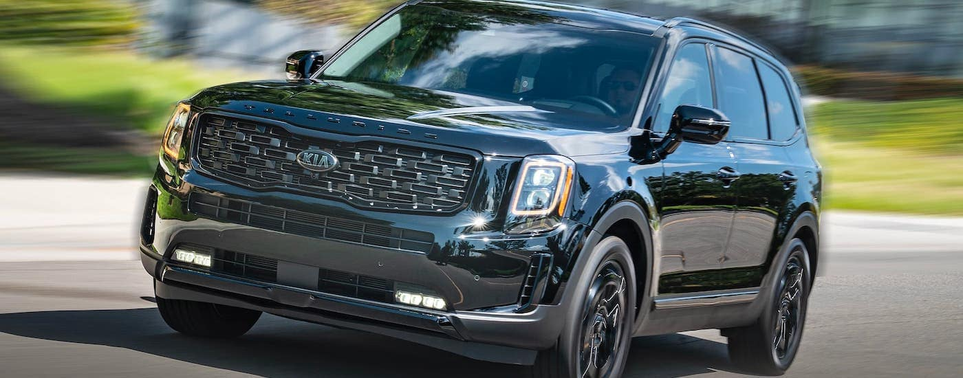 A black 2021 Kia Telluride is driving on a street near Freehold, NJ.