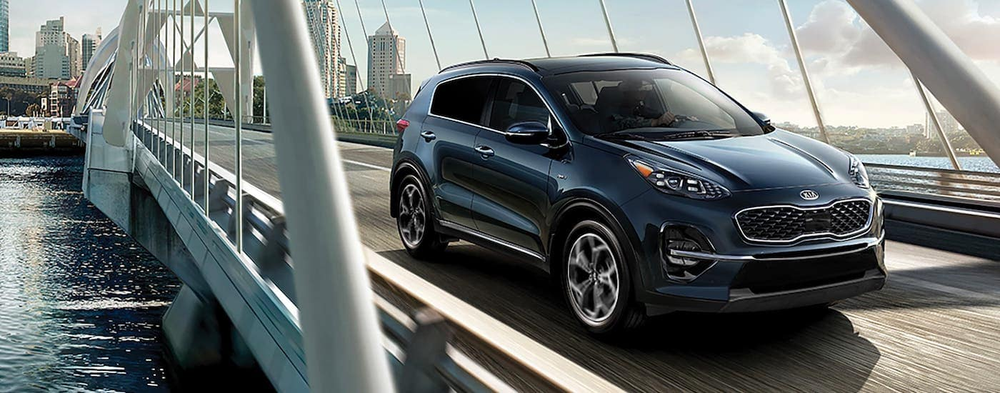 A blue 2021 Kia Sportage from a Kia dealership near Lakewood, NJ, is driving over a bridge.