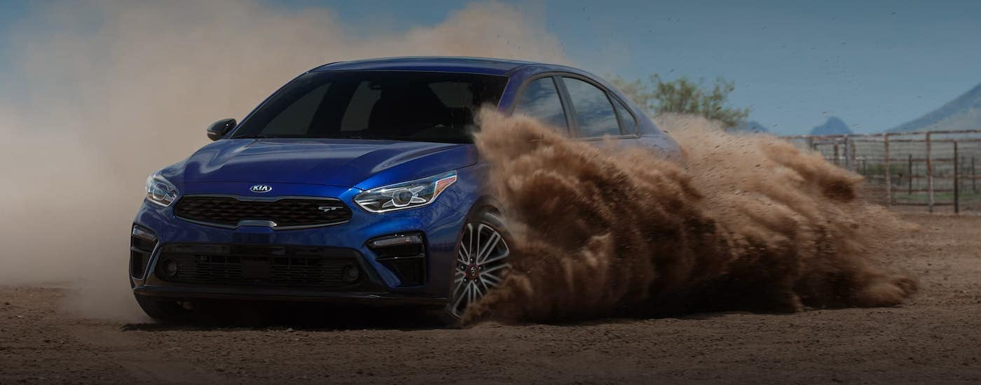 A blue 2021 Kia Forte is kicking up dirt in a field.