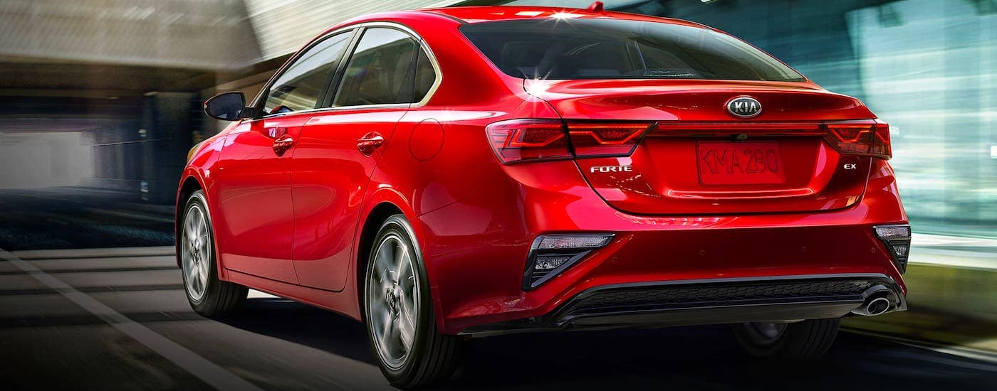 A red 2021 Kia Forte is shown from the rear driving on a street.