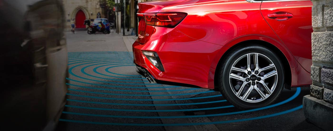 A red 2021 Kia Forte is backing up with simulated safety features.