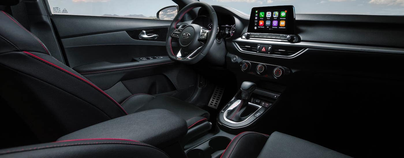 The black interior of a 2021 Kia Forte is shown with red accents.
