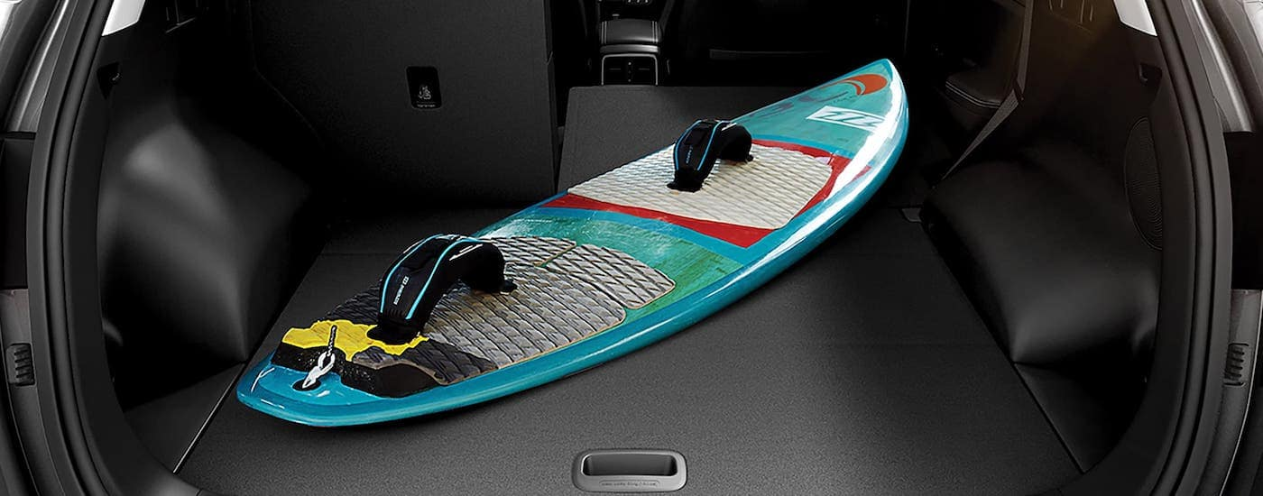 A teal wake board is shown in the cargo area of a 2021 Kia Sportage.