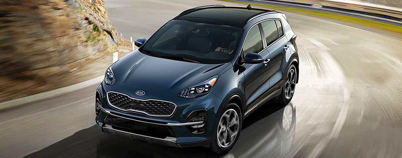 A dark blue 2021 Kia Sportage is driving on a winding road away from a city.