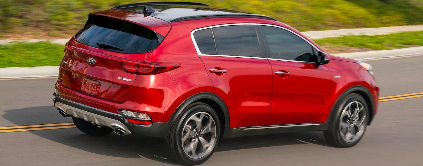 A red 2021 Kia Sportage is driving on an empty highway.