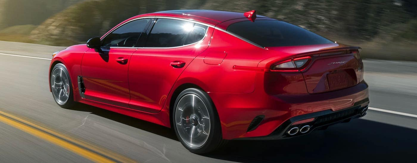 A red 2021 Kia Stinger is driving on a highway and shown from the rear.